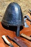 中世纪圆锥形盔甲也叫与鼻甲的诺曼底头盔显示与在orang和轻的战斧头显示的刀子 免版税库存照片