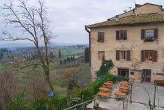 中世纪大厦的外部与一家餐馆的在早期的春天在圣吉米尼亚诺,意大利 库存照片