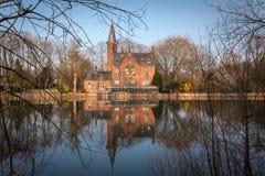 中世纪大厦(城堡)在Love湖, Minnewater公园在布鲁日,比利时 图库摄影