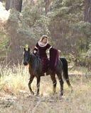 中世纪妇女骑乘马在森林里 免版税库存照片
