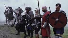 中世纪年龄的战士在抽烟的争斗前站立 股票录像