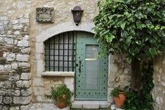 中世纪房子的老窗口和门在树下 免版税库存图片