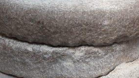 中世纪手主导的磨石研的麦子特写镜头英尺长度  与五谷的古老手磨器石头手动压榨机 沐浴快乐的头发长的人湿年轻人 影视素材