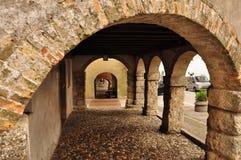 中世纪拱廊在圣达尼埃莱,弗留利,意大利村庄  免版税库存图片