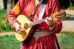 中世纪明亮的衣裳戏剧的音乐家在琵琶 中世纪音乐和文化节日  免版税库存照片