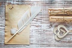 中世纪板料纸卷饰以羽毛在葡萄酒木头b的木心脏 免版税库存照片