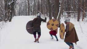 中世纪法兰克人,爱尔兰语,装甲的北欧海盗战士战斗在有剑盾的一个冬天森林里的 股票录像