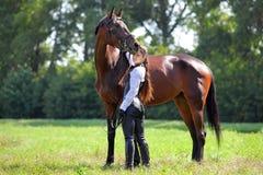 中世纪的美丽的女孩给与马的姿势穿衣 免版税图库摄影
