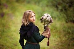 中世纪礼服的女孩拿着在她的胳膊的一头猫头鹰 免版税图库摄影