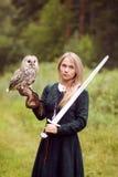 中世纪礼服的女孩拿着在她的胳膊的一头猫头鹰 免版税库存图片