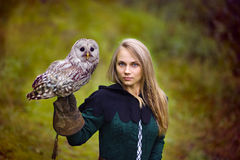 中世纪礼服的女孩拿着在她的胳膊的一头猫头鹰 免版税库存照片