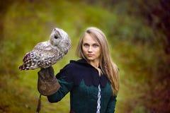 中世纪礼服的女孩拿着在她的胳膊的一头猫头鹰 库存图片
