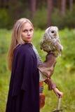 中世纪礼服的女孩有拿着猫头鹰的剑的 图库摄影