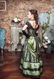 中世纪礼服的美丽的妇女在壁炉附近 免版税库存图片