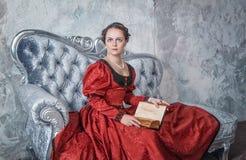 中世纪礼服的美丽的妇女在有书的沙发 免版税图库摄影