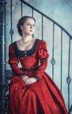 中世纪礼服的美丽的妇女在楼梯 库存图片