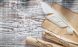 中世纪羊皮纸卷在葡萄酒木板饰以羽毛 库存图片