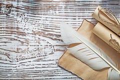 中世纪羊皮纸在葡萄酒木板滚动羽毛 免版税库存照片