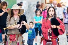 中世纪衣服的年轻风笛球员 库存图片