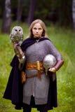 中世纪装甲的女孩,拿着猫头鹰 库存图片