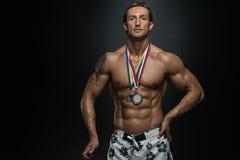 中古时期显示他赢取的奖牌的运动员竞争者 免版税库存图片