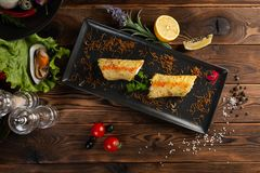 中国三文鱼rosti用在黑色的盘子的香料 免版税库存照片