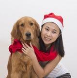 中国与她的狗的女孩佩带的圣诞节帽子 免版税库存图片