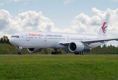 中国东方航空股份有限公司离开现用跑道的波音777-300ER 免版税库存照片