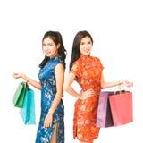 中国举行购物袋、春节或者shopaholic女孩概念的qipao传统礼服的两名亚裔妇女 免版税图库摄影