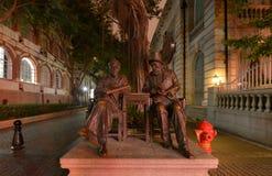 中国人和欧洲人贸易商古铜色雕象晚上,冬天,沙面岛 免版税库存照片