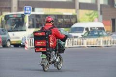 中国人在e自行车的麦克唐纳发运 图库摄影