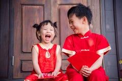 中国传统服装的愉快的亚裔兄弟姐妹 免版税库存图片