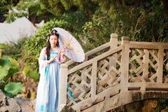 中国传统hanfu礼服举行纸umberalla的端庄的妇女在一座石桥梁 库存图片