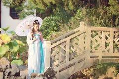 中国传统hanfu礼服举行纸umberalla的端庄的妇女在一座石桥梁 免版税库存照片