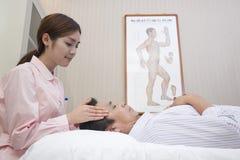 给中国传统医疗面部按摩的年轻女按摩师 库存照片