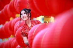 中国传统红色礼服的亚裔美丽的女孩 免版税库存图片