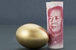 中国元金钱用在平静的黑暗的背景的金鸡蛋 免版税库存图片