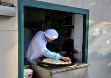 中国厨师在长柄浅锅上海中国安置传统酥皮点心 免版税库存照片