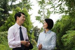 中国同事谈话在公园 库存图片