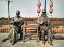 中国和西部商务伙伴雕塑  库存图片