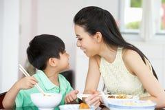 中国在家坐吃的母亲和儿子 免版税库存图片