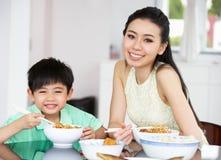 中国在家坐吃的母亲和儿子 库存图片