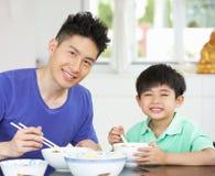 中国在家坐吃的父亲和儿子 免版税库存照片