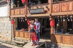 年轻中国夫妇穿戴了与传统服装,当握在一个古老大厦前面的手在ShuHe老镇时 库存照片