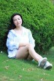 中国女孩读书在公园 有书的白肤金发的美丽的少妇坐草 库存照片