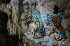 中国女孩绘画在墙壁上的在洞看起来  库存图片