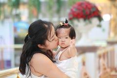 中国妇女亲吻她的购物中心的甜女婴 免版税库存照片