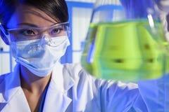中国妇女科学家绿色烧瓶在实验室 免版税库存图片
