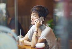 中国妇女谈话在咖啡店的智能手机 库存图片
