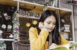 中国学生坐椅子咖啡屋子外 库存图片